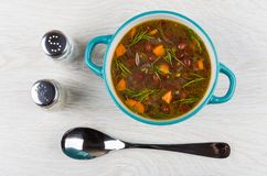 Kidney bean soup in blue bowl, salt, pepper and spoon. On wooden table. Top view Royalty Free Stock Photo