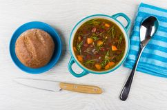 Kidney bean soup in bowl, spoon, bread in saucer, knife Royalty Free Stock Photography