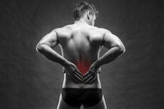 Kidney pain. Man with backache. Handsome muscular bodybuilder posing on gray background. Black and white photo with red dot royalty free stock images