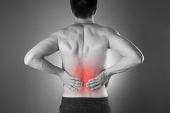 Kidney pain. Man with backache. Pain in the man's body. Black and white photo with red dot royalty free stock images