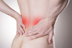 Kidney pain. Man with backache. Pain in the man's body. On a gray background stock images