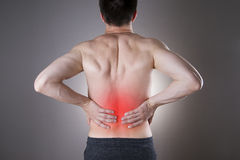 Kidney pain. Man with backache. Pain in the man's body. On a gray background with red dot Stock Photo