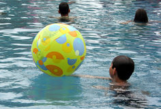 Kids. Playing with beach ball in pool Stock Photography