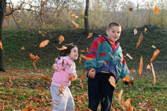 Kids. Little boy and girl playing with autumn leaves in the park Stock Photography