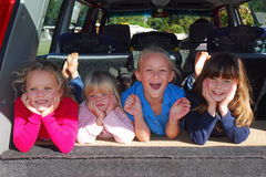 Kids. Four little Caucasian children with excited facial expression in the back of a red combi showing that they are ready to take off and want to hit the road stock image