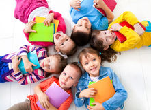 Kids. Six children lying on floor with books and smiling Royalty Free Stock Image