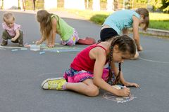 Kids absorbedly draw chalks on the pavement. In summer Royalty Free Stock Photos