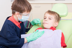 Kids acting as doctor and patient. In dental office. Fearless boy patient concept Stock Images