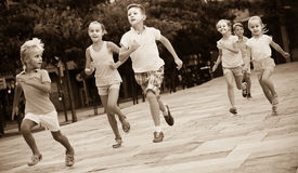 Kids actively playing and running together on street on summer d Stock Photography