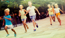 Kids actively playing and running together on street on summer d Royalty Free Stock Photography