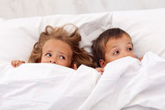 Kids afraid pulling the quilt on their heads. Kids afraid laying in bed and pulling the quilt on their heads stock photos