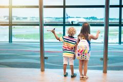 Kids travel and fly. Child at airplane in airport Stock Photos