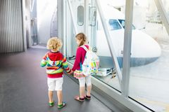 Kids travel and fly. Child at airplane in airport Royalty Free Stock Images