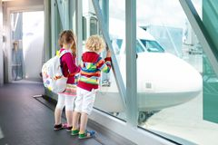 Kids travel and fly. Child at airplane in airport Royalty Free Stock Photo