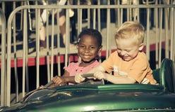 Kids on an amusement park ride. Two cute diverse kids having fun on an amusement park ride in the summertime Stock Photo