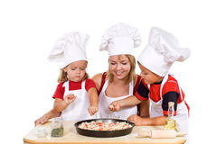 Kids And Their Mother Preparing A Pizza Royalty Free Stock Images