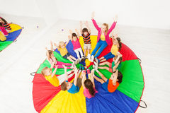 Kids and animator having fun playing circle games. Top view portrait of happy children and female animator playing circle games, sitting on colorful parachute in Royalty Free Stock Image