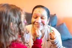 Kids applying make up to grandmother. stock image