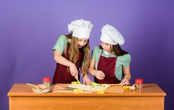 Kids aprons and chef hats cooking. Family recipe. Culinary education. Mothers day. Baking ginger cookies. Girls sisters. Having fun ginger dough. Homemade stock photo