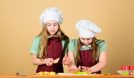 Kids aprons and chef hats cooking. Homemade cookies best. Family recipe. Cooking skill culinary education. Baking ginger. Cookies. Girls sisters having fun royalty free stock images