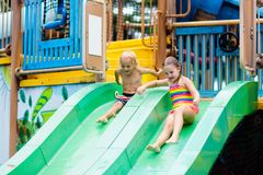 Kids at aqua park. Child in swimming pool. Kids play in aqua park. Children at water playground of tropical amusement park. Little girl and boy at swimming pool stock photo