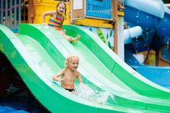 Kids at aqua park. Child in swimming pool. Kids play in aqua park. Children at water playground of tropical amusement park. Little boy at swimming pool. Child stock photos
