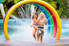 Kids at aqua park. Child in swimming pool. Kids play in aqua park. Children at water playground of tropical amusement park. Little girl and boy at swimming pool stock image