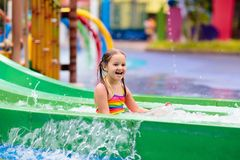 Kids at aqua park. Child in swimming pool. Kids play in aqua park. Children at water playground of tropical amusement park. Little girl at swimming pool. Child stock photo