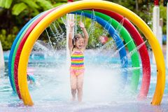Kids at aqua park. Child in swimming pool. Kids play in aqua park. Children at water playground of tropical amusement park. Little girl at swimming pool. Child royalty free stock images