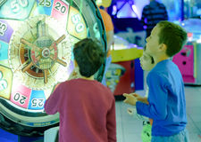 Kids at the Arcade. KFAR SABA, ISRAEL - DEC. 12, 2015: 8 year old kids having fun at the arcade with video games, lottery machines, tickets, and prizes Royalty Free Stock Photography