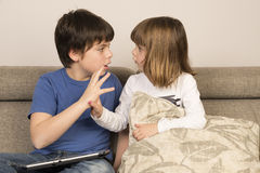 Kids arguing for playing with a digital tablet. On a sofa royalty free stock photo