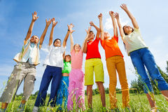 Kids with arms up stand straight in row. In green field outside Stock Photo