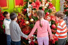 Kids around Christmas tree Royalty Free Stock Photos