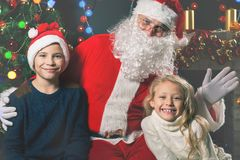 Kids around Santa Claus tell him they wishes, Christmas eve Stock Photos