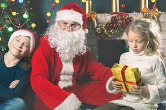 Kids around Santa Claus tell him they wishes, Christmas eve Stock Photography