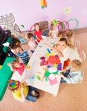 Kids around table in kindergarten class from above stock photos