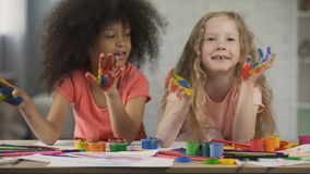 Kids art club. Multiracial children waving painted palms and singing, childhood