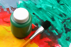 Kids artistic expressions-green. Water based paints and brush on a painted background Stock Photos