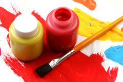 Kids artistic expressions-red and yellow. Water based paints and brush on a painted background Royalty Free Stock Images