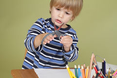Kids Arts and Crafts Activity Child Learning to Cut with Scissor. Arts and crafts activity, child learning to cut with scissors, learning and education concept royalty free stock photography