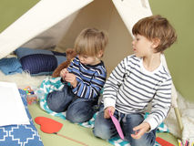 Kids Arts and Crafts Activity, Playing in Teepee Tent. Kids engaged in arts and crafts activity, playing in a teepee tent at home Stock Photography