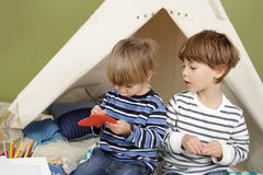 Kids Arts and Crafts Activity, Playing in Teepee Tent. Kids engaged in arts and crafts activity, playing in a teepee tent at home Royalty Free Stock Photo