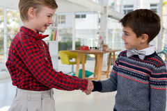 Kids as business executives shaking hands stock photos