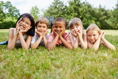 Kids as friends at meadow. Resting on the grass Stock Photography