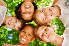 Kids as international team. In a circle smiling in summer Royalty Free Stock Images