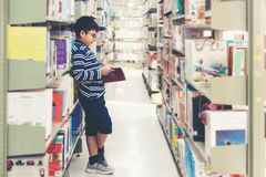 Kids asia boy reading books for education and go to school in library stock photo