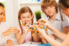 Kids assembling atomic chain with molecular model. Four students, teenagers, assembling atomic chain with molecular model at chemical laboratory Royalty Free Stock Image