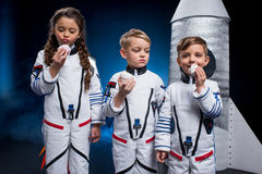 Kids in astronaut costumes. Three cute kids in astronaut costumes eating sweets standing near rocket Royalty Free Stock Photo