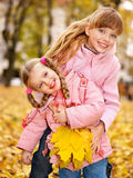 Kids in autumn leaves. Royalty Free Stock Image