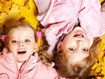 Kids in autumn orange leaves. Royalty Free Stock Images